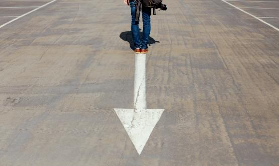 A person standing on an arrow in the road