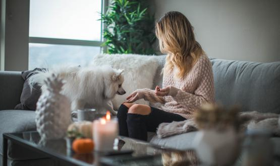 A woman in a sweater in her home with a dog
