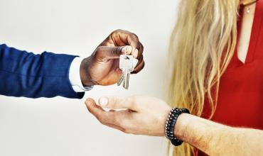 A man in a suit handing a woman a set of house keys