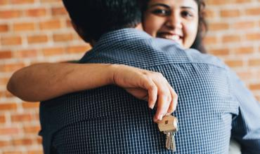 a woman holding a house key hugging a man