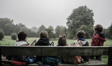 Four children sitting on a bench with their backs to the photographer