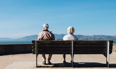 Older couple sitting on a bench facing mountains