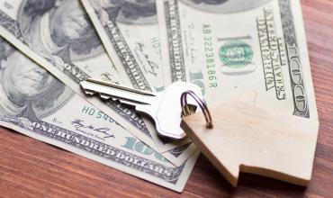 A key with a house keychain sitting on four dollar bills