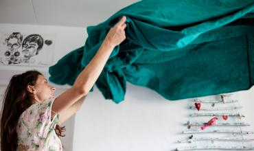 a woman making a bed with a turquoise sheet