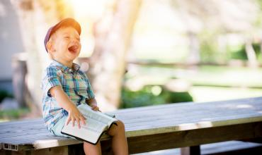 a boy laughing on a bench