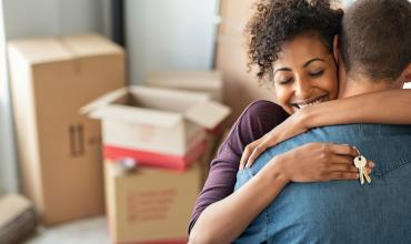 two people hugging in front of moving boxes holding a key