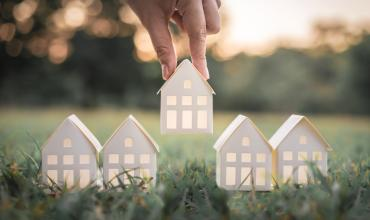 Paper houses being placed on the grass by a hand above