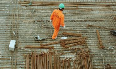 A man in an orange suit walking a construction site