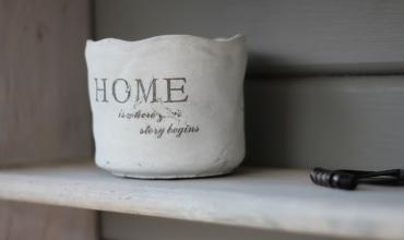 A ceramic vase on a shelf that says HOME on it