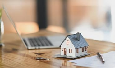 Miniature house beside a keyboard and paperwork on desk