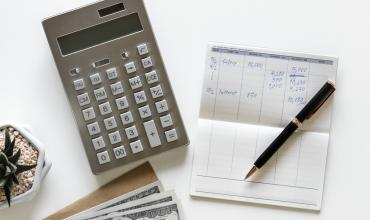 a table with a calculator, checkbook and pen