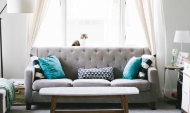 A gray couch with blue pillows and a coffee table in front of it