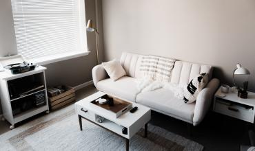 A white sofa and coffee table on a light blue rug