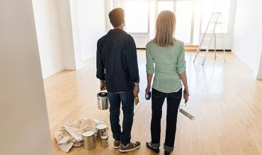 two people with painting supplies standing in a living room