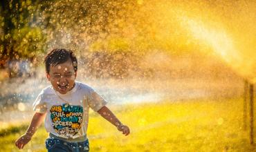 A little boy running through the sprinklers on a sunny day