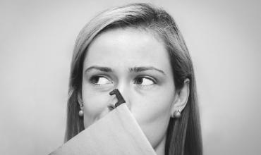 a woman holding a folder in front of her face