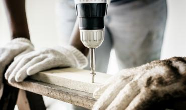 A worker using a power drill