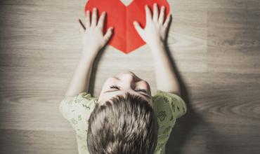 child with a red paper heart