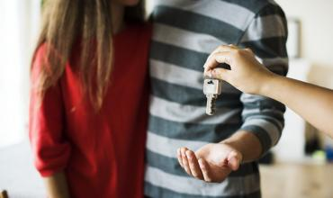 a couple being handed a house key