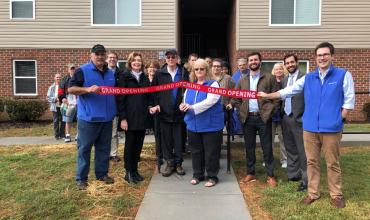 A group of people cutting a ribbon outside of the apartment development