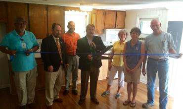 group of people around a ribbon getting ready to cut it inside a home