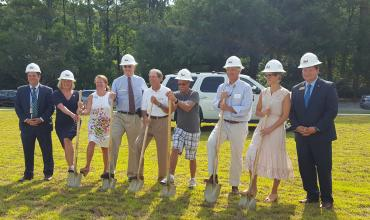 People in hard hats participating in a ground breaking ceremony