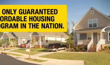 """Photo of houses with text over it reading """"the only guaranteed affordable housing program in the nation"""""""