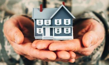 Person in a military uniform holding a little blue house