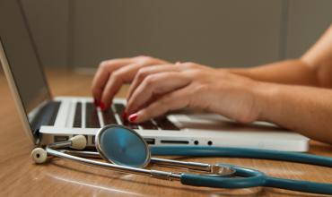 A stethoscope laying next to a person typing on a computer