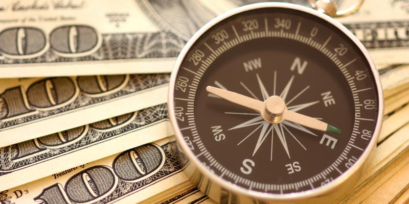 A compass on top of money