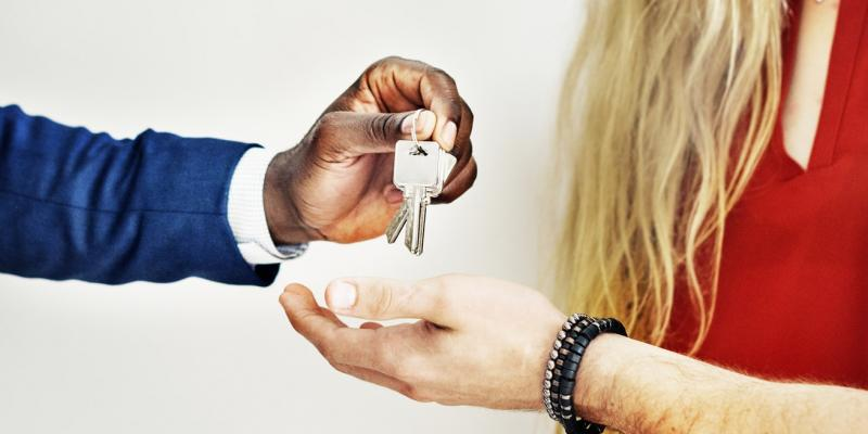 One person handing another a key