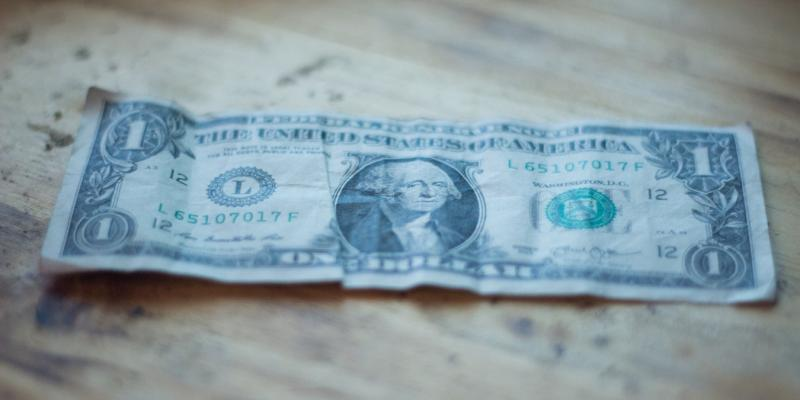 a one dollar bill on a wooden table