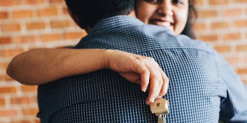 a woman holding a house key hugging a man
