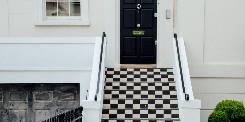 A black house door above a checkerboard staircase