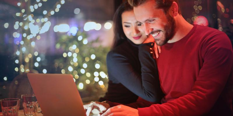 Couple looking at computer screen, with Christmas tree in background