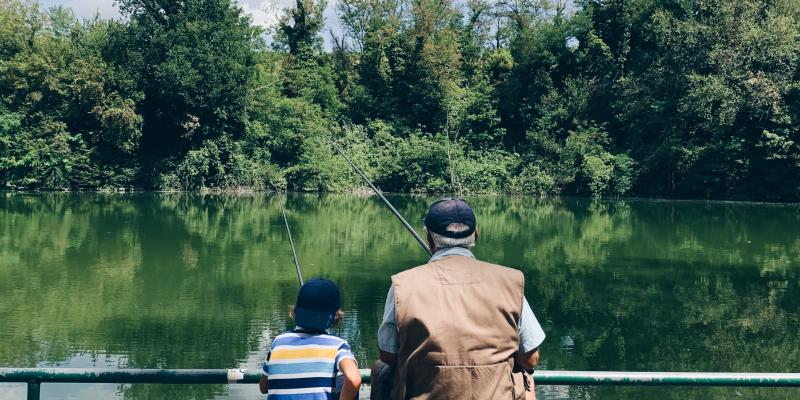 A man and a small boy fishing together seen from the back