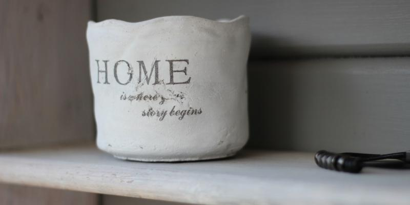 A coffee cup that says home on it