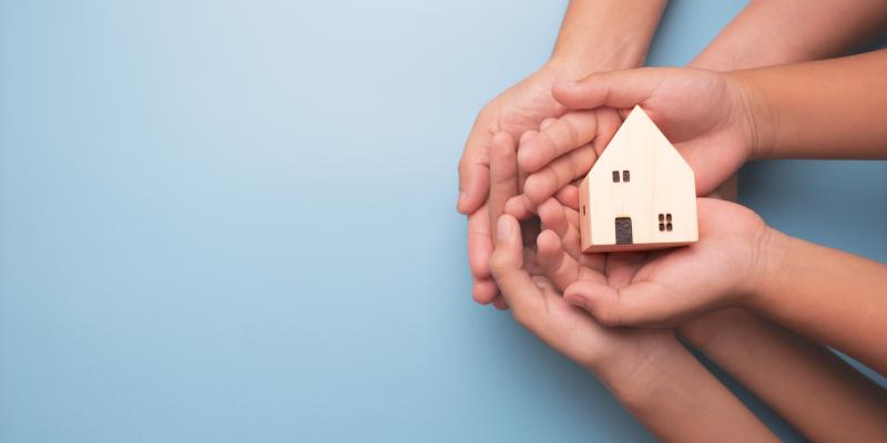 Hands holding up a little house
