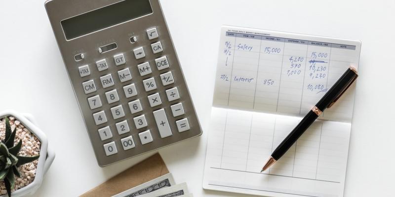 checkbook with pen and calculator on white desk
