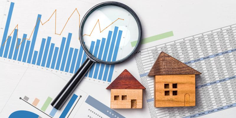 Two little wooden houses and a magnifying glass over papers with graphs and charts on them
