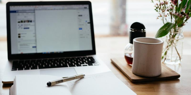 a table with a computer, journal and coffee