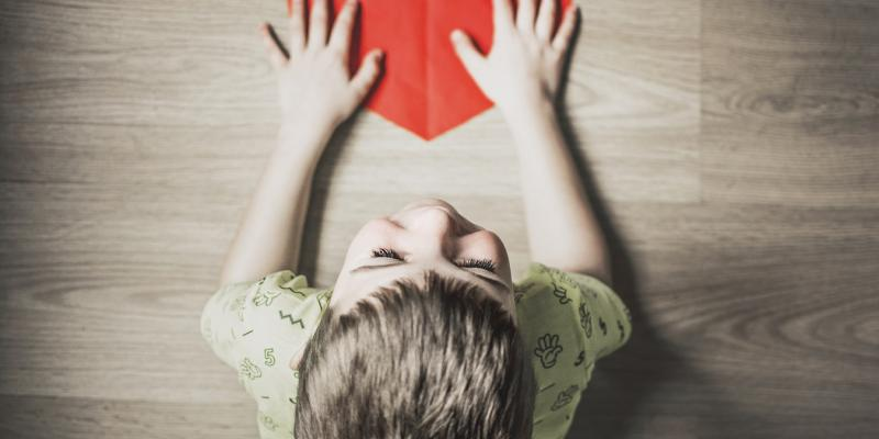 a kid with a red paper heart