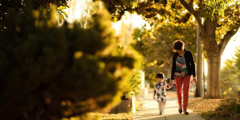 a woman and a boy holding hands walking down a sidewalk