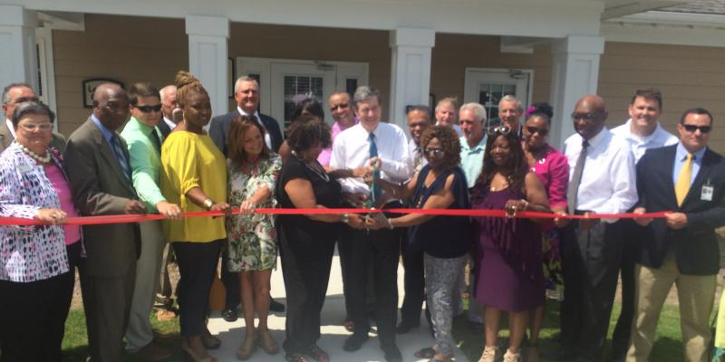a ribbon cutting ceremony on a front porch
