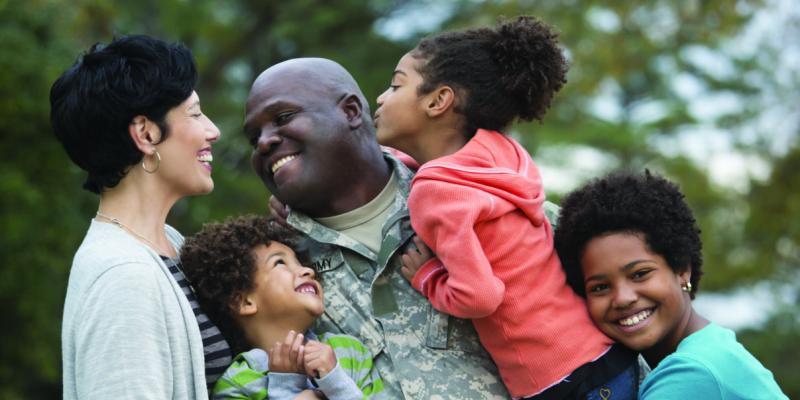 a veteran in uniform hugging his family