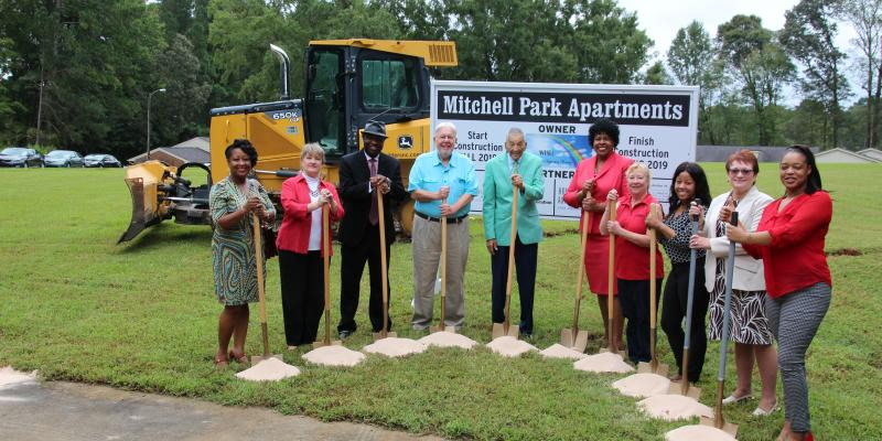 people holding shovels at a groundbreaking ceremony