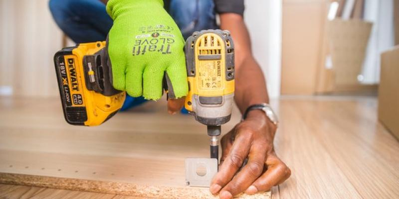Guy drilling a hole into hardwood floor